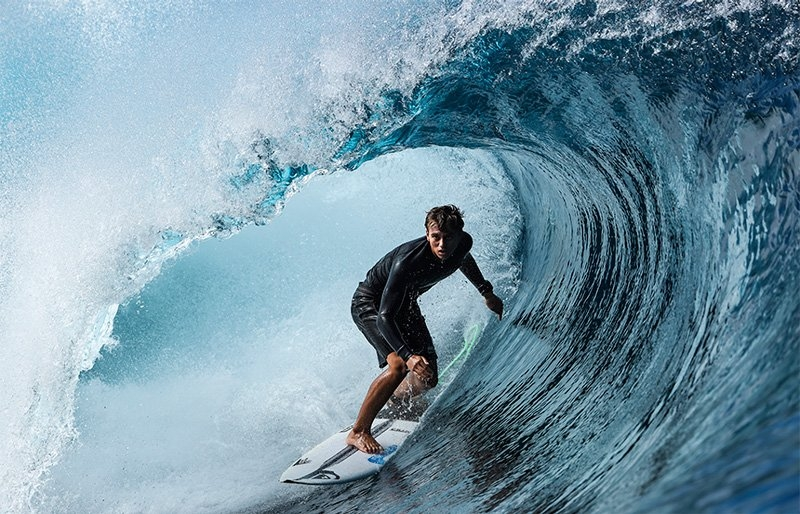 A surfer rides inside the barrel of a wave